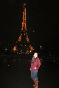 Ashley during white snowfall in Paris, France in front of the Eiffel Tower